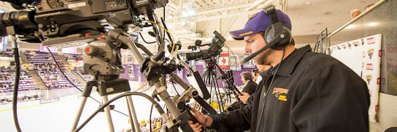 Një student operon me një kamerë televizive për të regjistruar një lojë lokale të hokejve në akull.